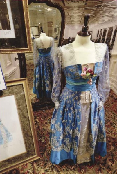 The dress was reproduced from an original designer's sketch (shown in the lower left corner).   Photo Credit: Cedar Bay Entertainment. Image from postcard purchased by author in gift shop.