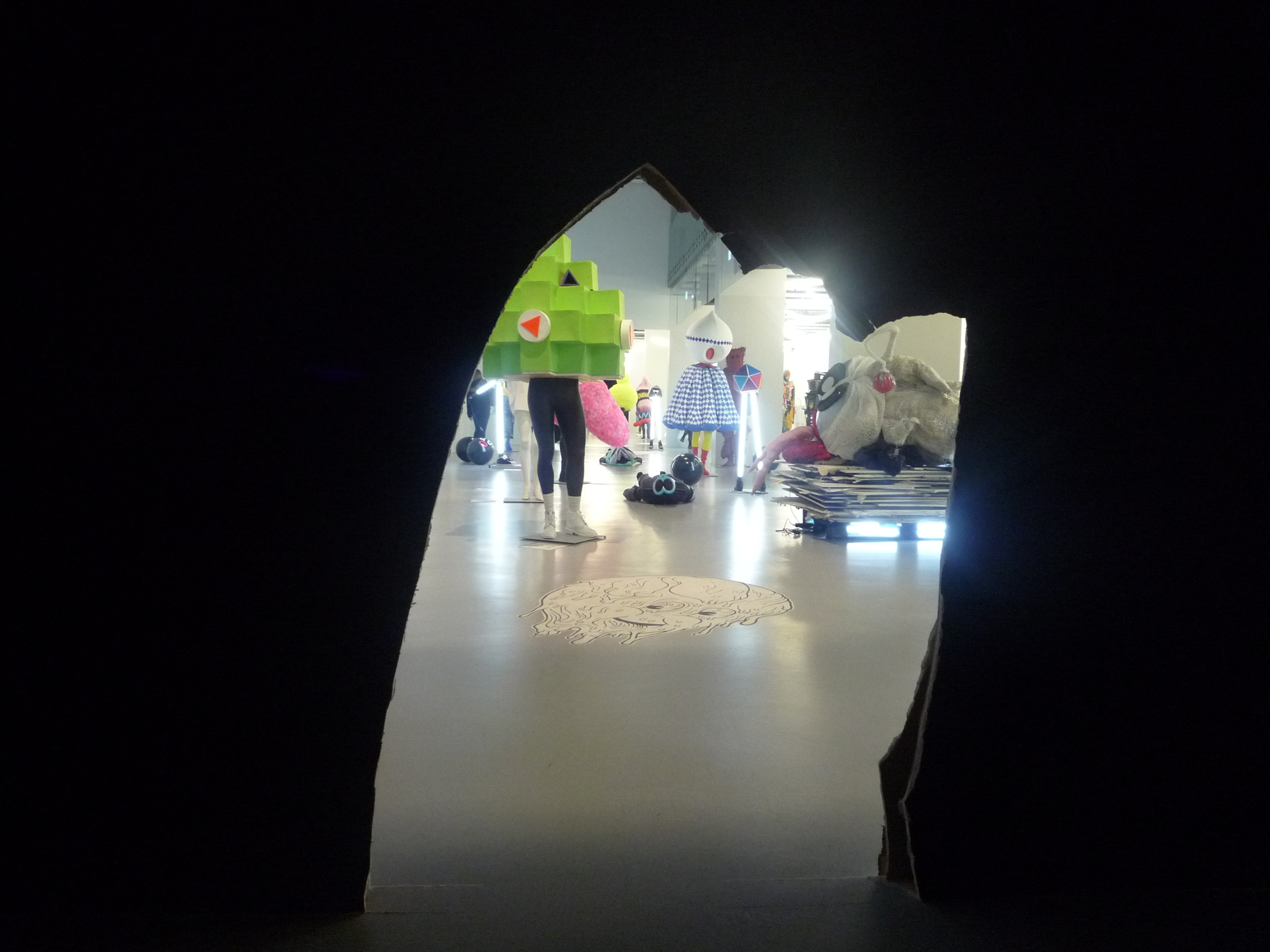 View of the main display through a hole created in a passageway by a furious monster