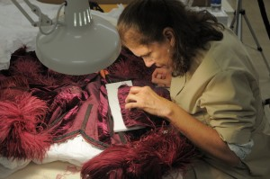 No gloves: conservator Cara Varnell performs delicate conservation work on the burgundy ball gown from Gone With the Wind. Photo by Pete Smith