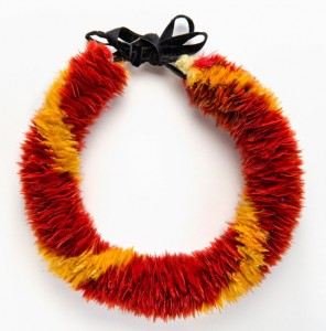 Lei hulu (feather lei), 19th century. Yellow 'ō'ō (Moho sp.) feathers, red Kuhl's lorikeet (Vini kuhlii) feathers, and black ribbon, 14 3/8 x 1 1/2 in. (36.5 x 3.8 cm). Bernice Pauahi Bishop Museum, Ethnology Collection
