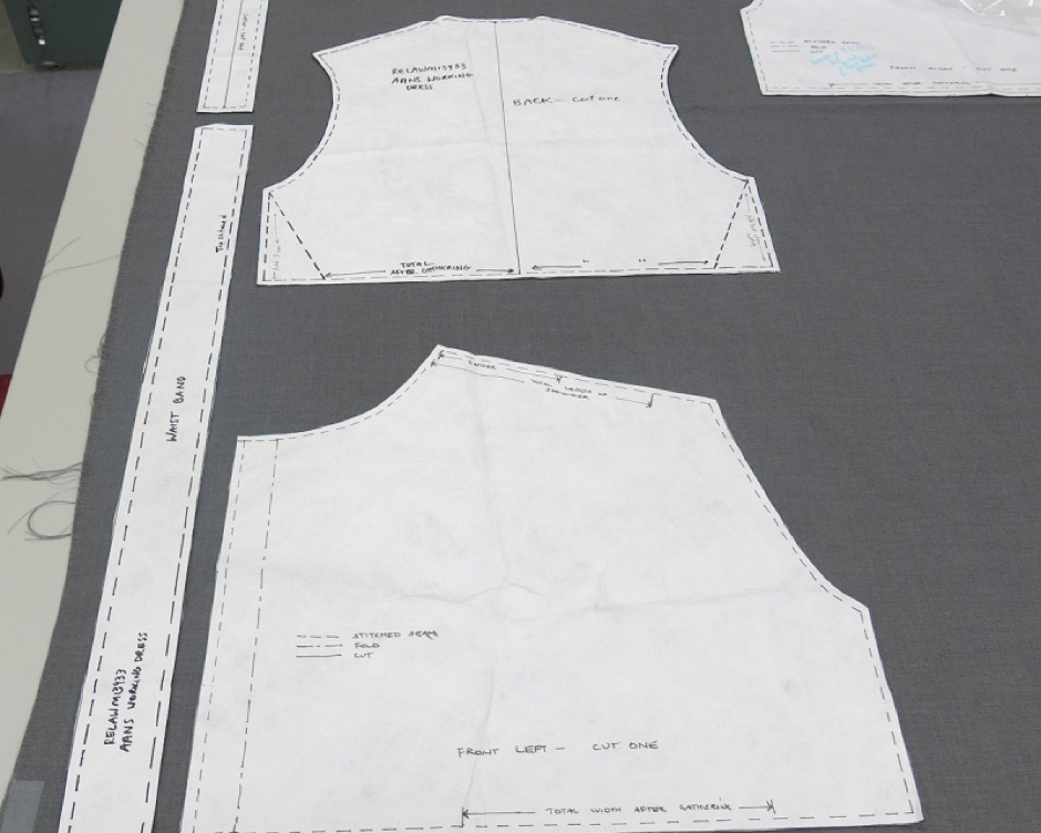 Paper pattern copies laid out over the poly-cotton fabric for tracing. Darts, gathers and seams are marked out.