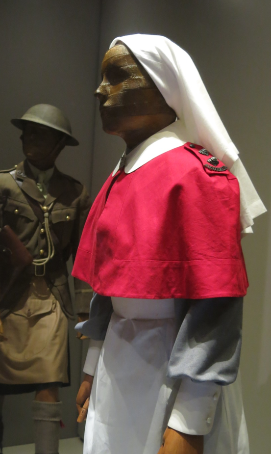 The Australian Army Nursing Service figure, with grey ward dress replica worn underneath period apron, collar, cuffs, and cape. Australia in the Great War exhibition.