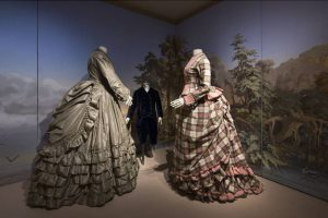 The 19th century garments before a romantic painted background